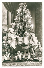 happy kids with christmas tree, gifts and vintage toys. antique