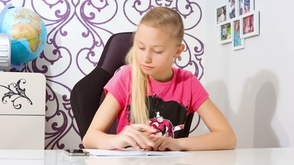 Girl doing homework and looking on smartphone