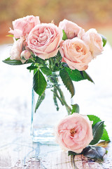 Delicate pink roses in a glass vase on the table.