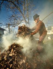 Old farmer burning dead leaves