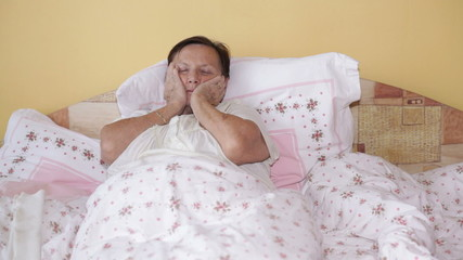 Ill senior woman in bed with painful toothache.