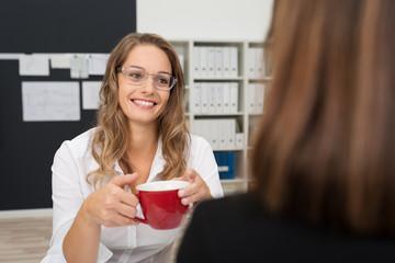 kolleginnen im büro trinken kaffee zusammen
