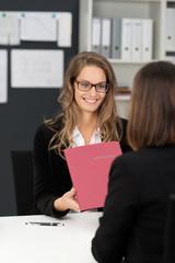 frau im büro überreicht bewerbungsmappe