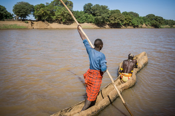 Men cross the Omo River near Turmi using a wooden boat, Ethiopia