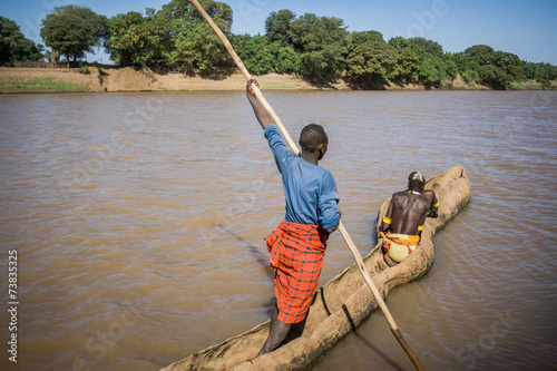 Papiers peints Autre Afrique Men cross the Omo River near Turmi using a wooden boat, Ethiopia