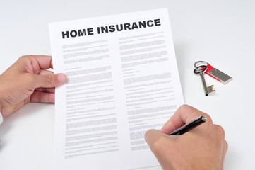 a young man signing a home insurance policy