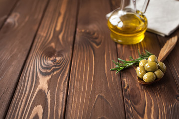 green olives and olive oil on wooden table