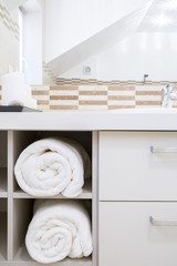 Towels in modern bathroom's cupboard