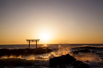 日の出と波しぶきのシルエット