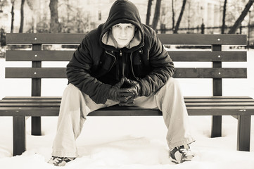 young man in casual clothes sitting on winter bench