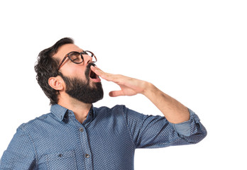 Young hipster man yawning over white background