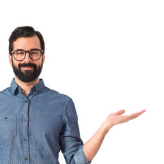 Young hipster man holding something over white background