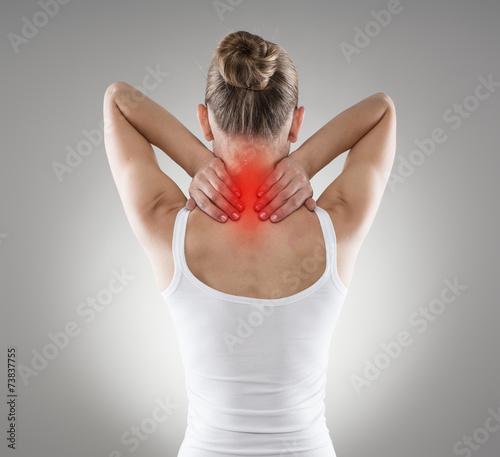 Leinwanddruck Bild Injured neck. Young female suffering from spine disease.
