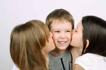 two teens girls kissing little laughing boy