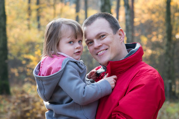Father and daughter in autumn forest