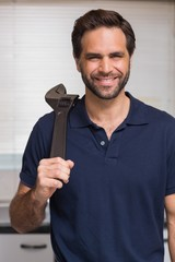 Casual man holding a wrench