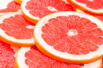 Red background of grapefruit slices