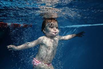 baby  in water park swimming underwater