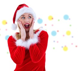Composite image of festive blonde with hands on face