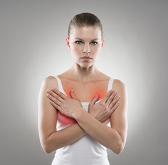 Young female examining her breast. Chest pain, therapy and care