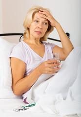 pensioner  in bed with pills and glass of water