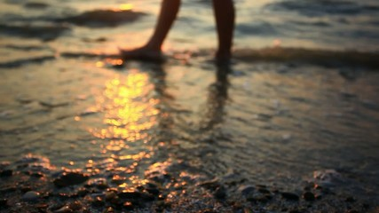 Feet of a young woman walking on the beach at sunset. HD.