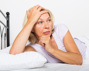 thoughtful mature woman   in bedroom