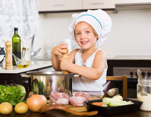 Little girl cooking soup in pan