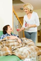 retirement home employee offering  mixture to mature patient