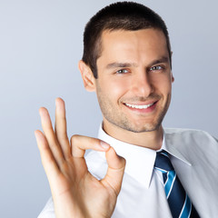 Businessman with okay gesture, against grey