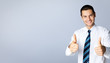 Smiling businessman with thumbs up gesture, on grey