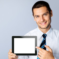 Businessman showing blank tablet pc, on grey