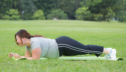 obese women planking on grass