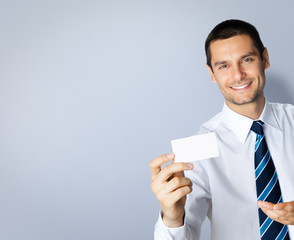 Businessman with business card, on grey