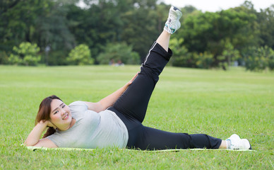 obese women side scissor kick exercise on grass