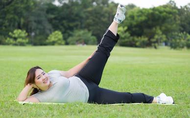 obese women side scissor kick exercise on grass