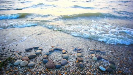 Christmas 2015 made of small stones on the sandy beach. HD.