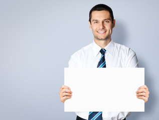 Businessman showing blank signboard, over grey
