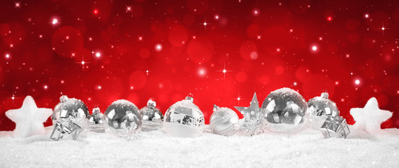 silver Baubles on snow with red sparkle background
