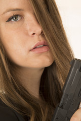 Close-up portrait of a woman holding a pistol with a somber expr
