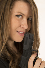 Close-up portrait of a woman holding a pistol with a smirk on he