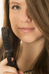 Young brunette woman with a pistol and her hair over one eye