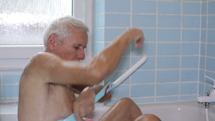 Senior man washing his body with bath brush.