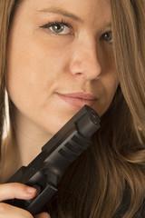 Protrait of a brunette woman peering over a black gun