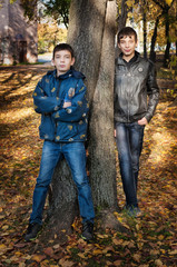 Two brothers standing near the tree
