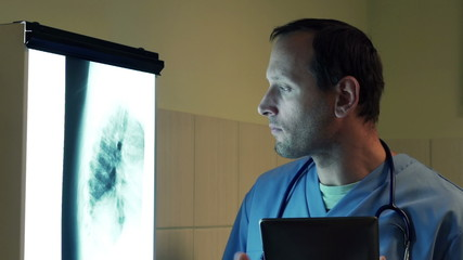 Male doctor checking lungs xray on tablet computer in hospital