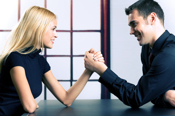 Couple or businesspeople fighting in arm-wrestling