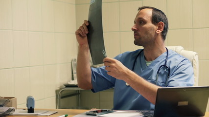 Male doctor checking and looking at xray in hospital