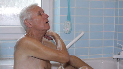 Senior man sitting in bath and using shower.