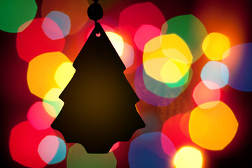 Christmas tree silhouette in front of a blurred color lights